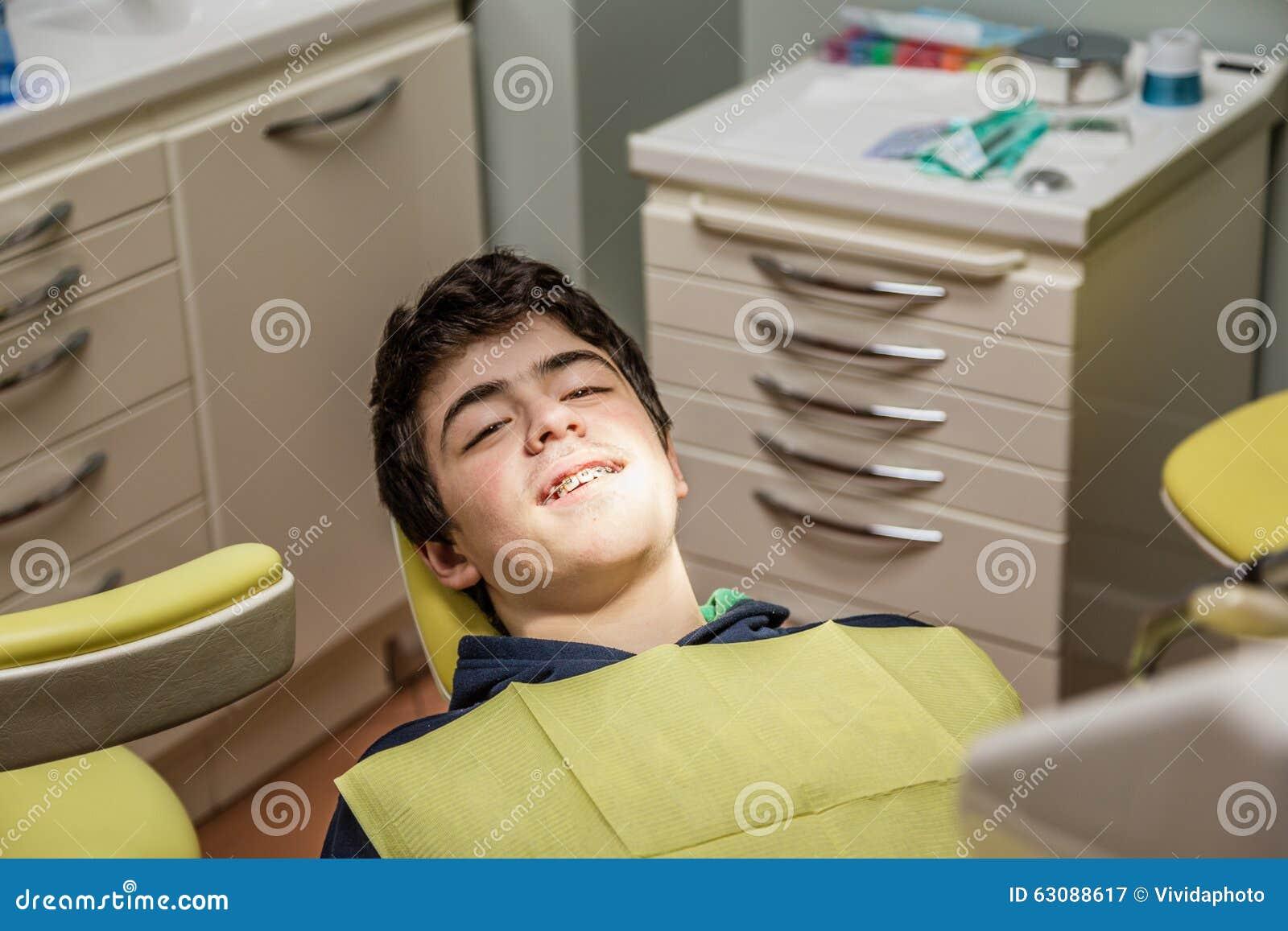 Download Garçon Sur Les Accolades D'apparence De Chaise De Dentiste Image stock - Image du adolescent, acné: 63088617