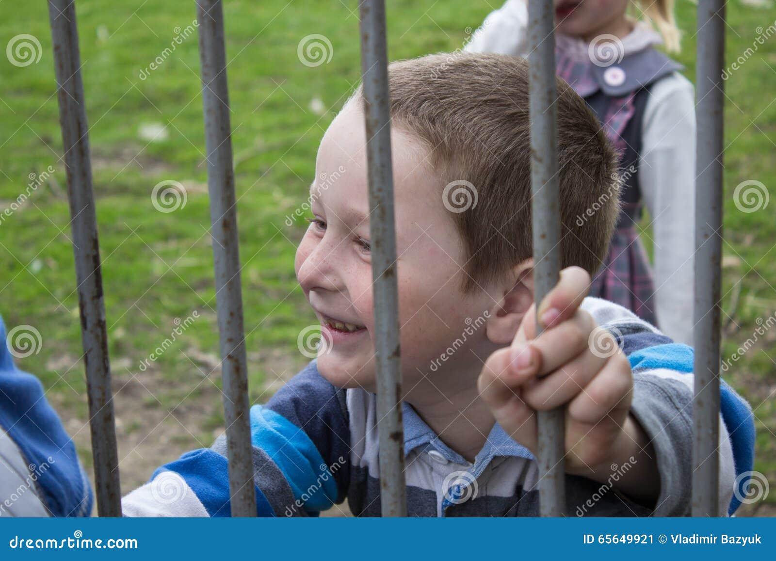 Garçon sur une barrière en métal