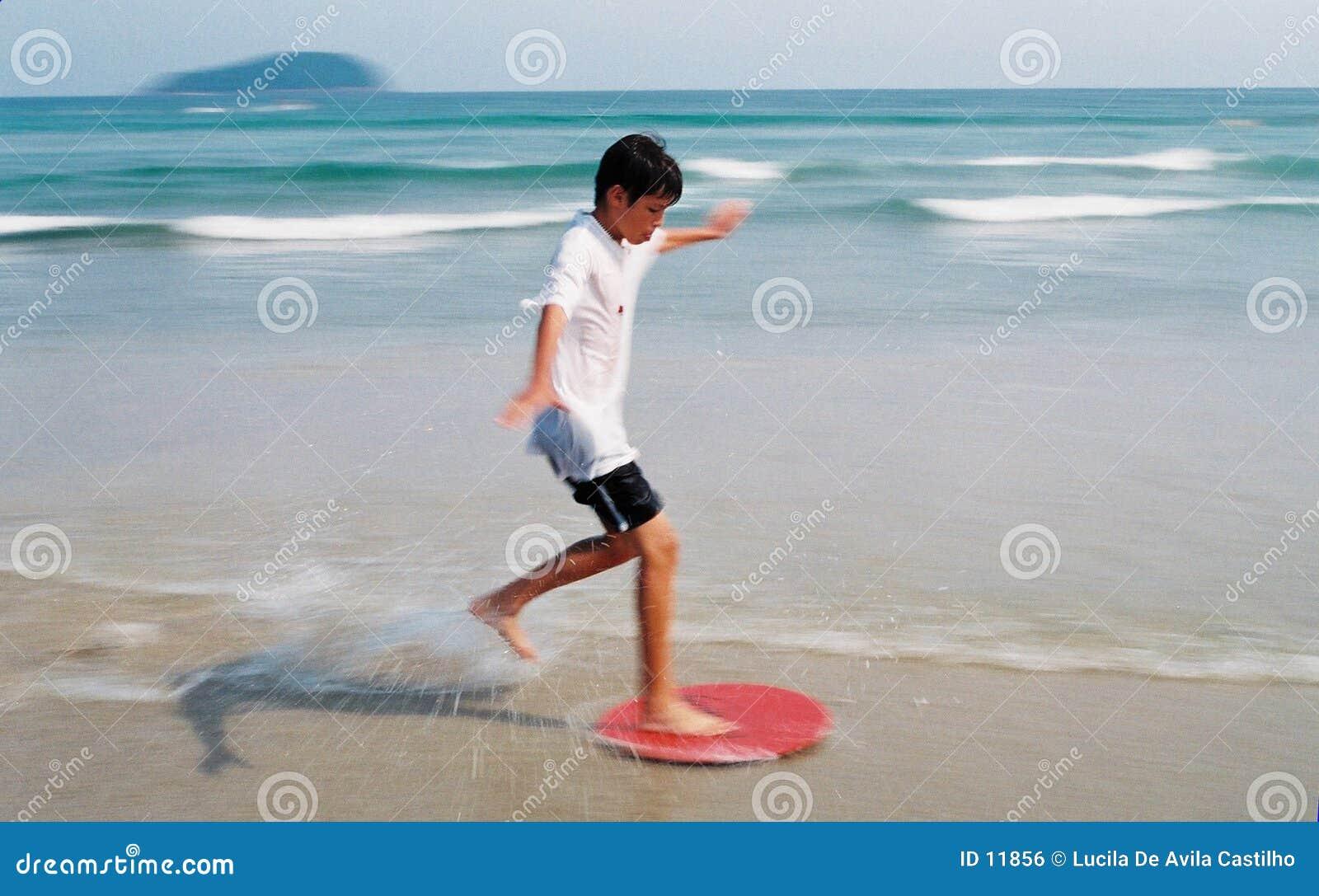Garçon surfant par des ondes
