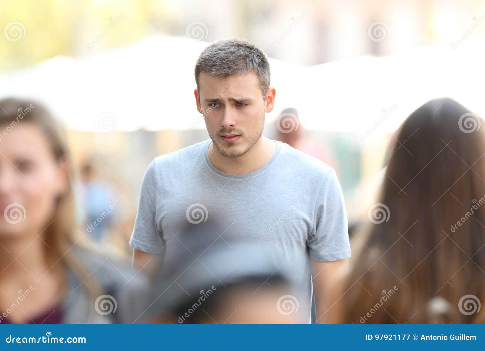 Garçon triste marchant sur la rue