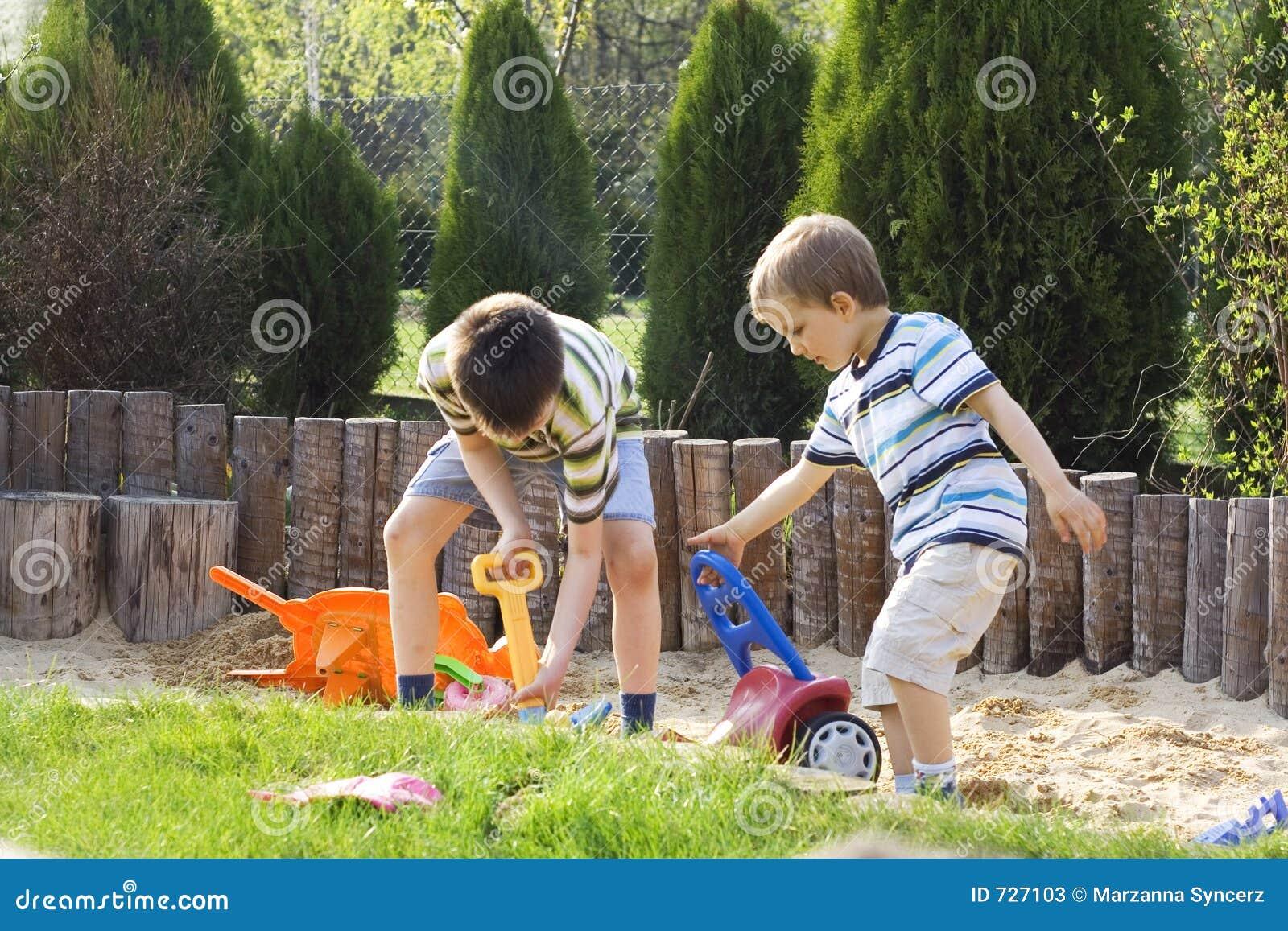 Garçons jouant en sable
