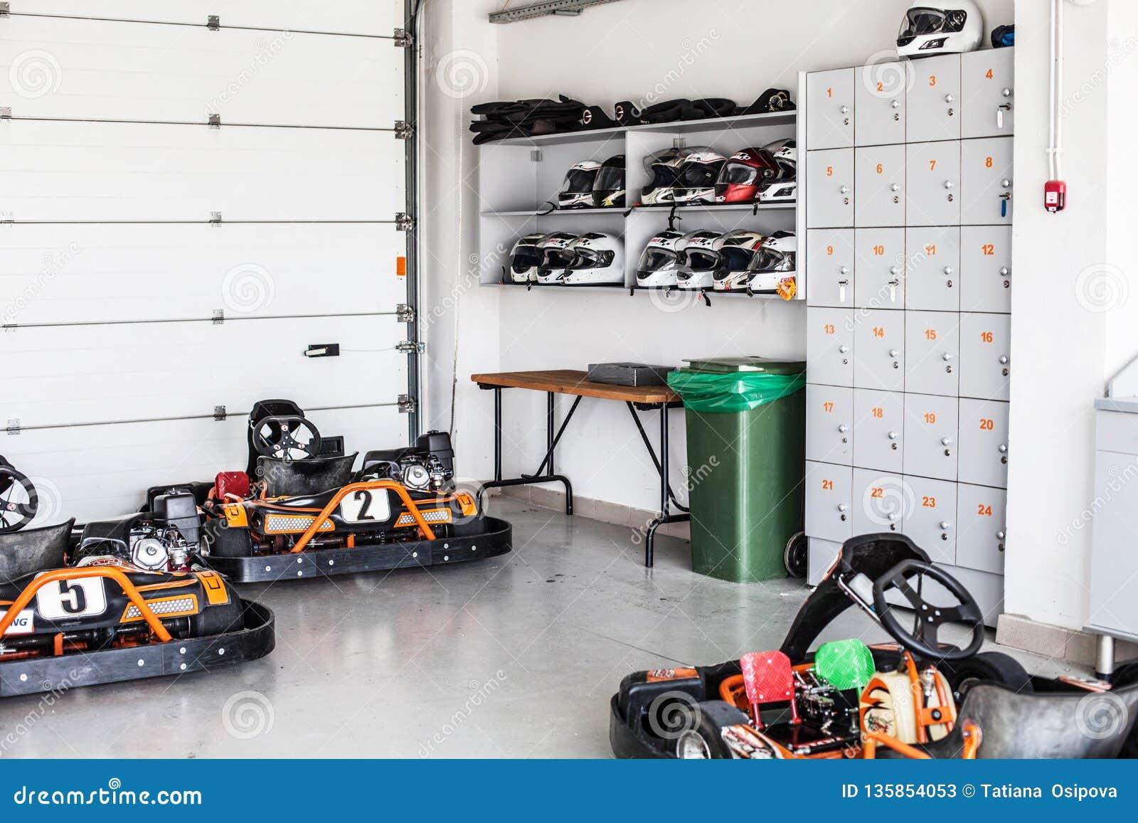 Garage för karting lagring, hyllor med hjälmar och lagringsaskar Sommar, aktiv familjgyckel eller sportar
