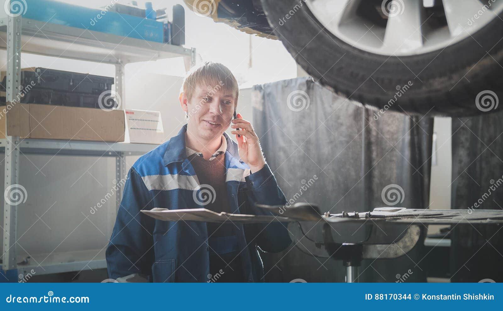 Garagebilservice - lyftbil för mekaniker en nära talar på mobiltelefonen