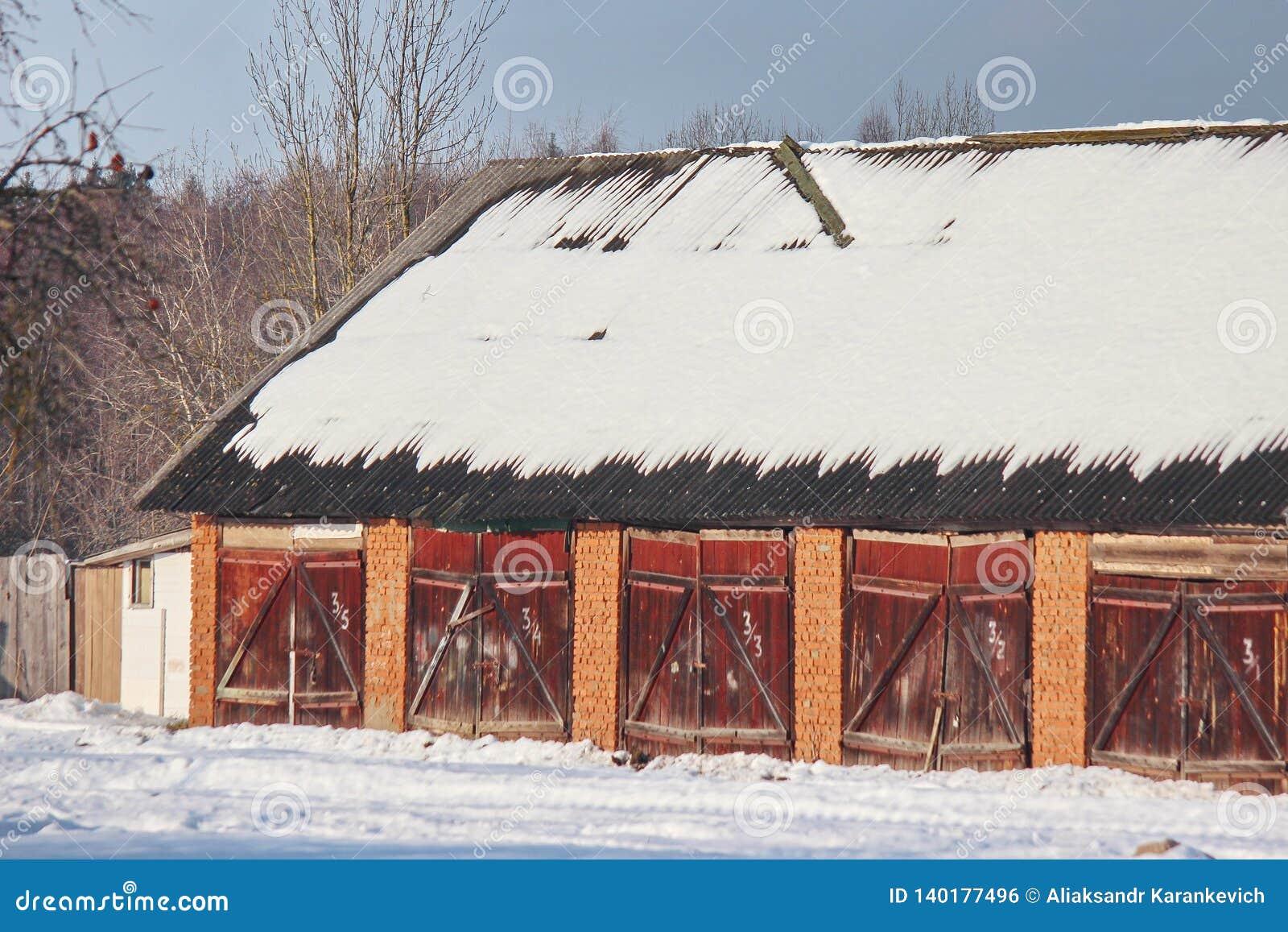 Garages ou hangars publics de village en hiver un jour ensoleillé La neige sur le toit est numérotée des entrées