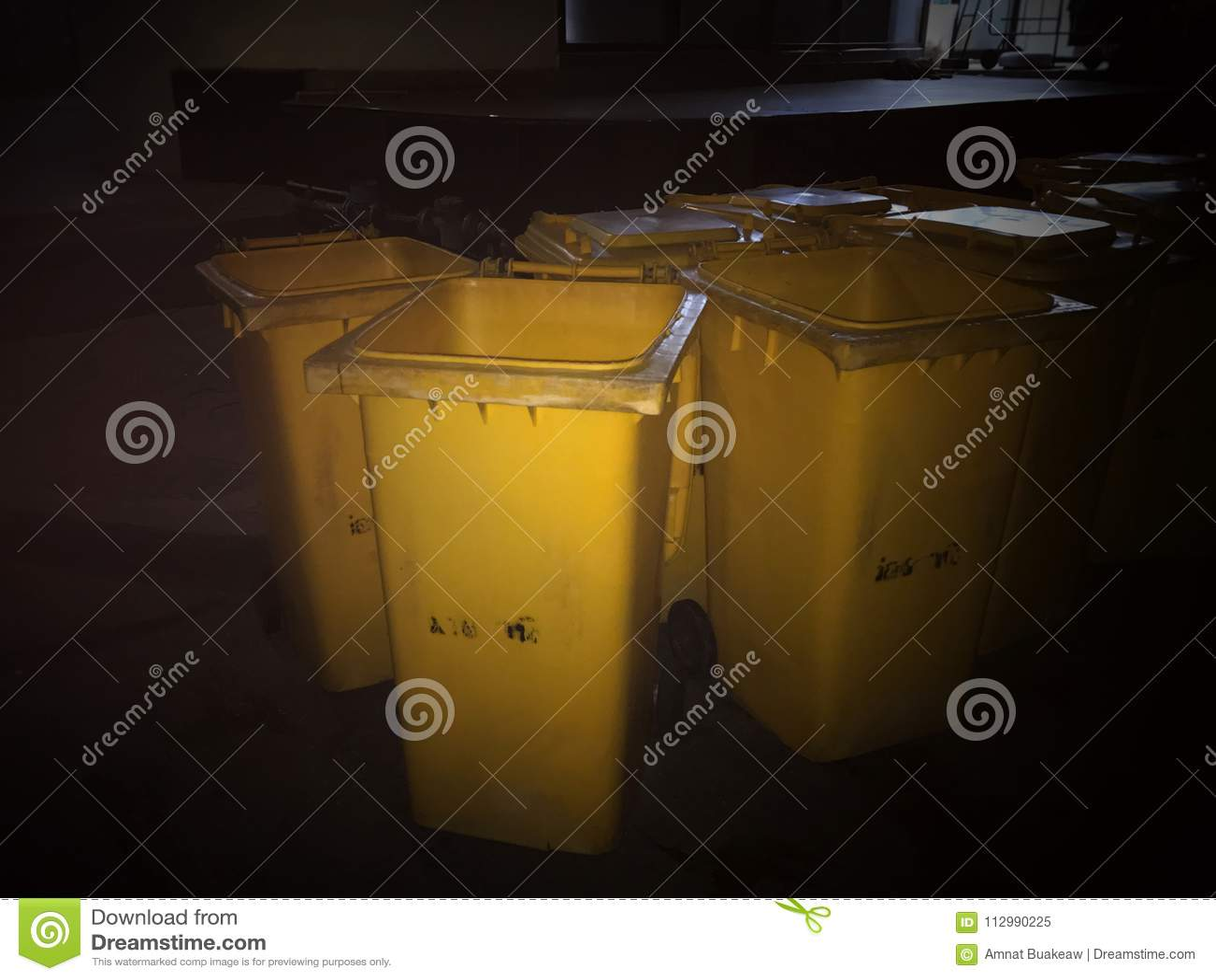 Garbage bin Yellow plastic bin trash at night time