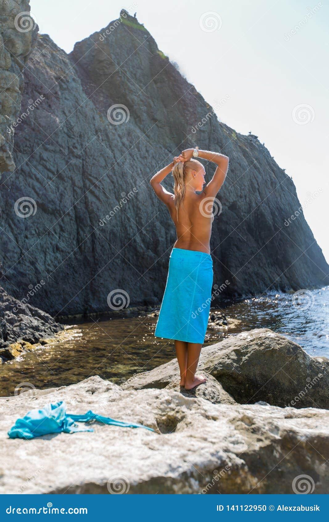 Garbnikująca blond z włosami żeńska osoba odpoczywa przy ustronnym miejscem dziki skalisty seashore