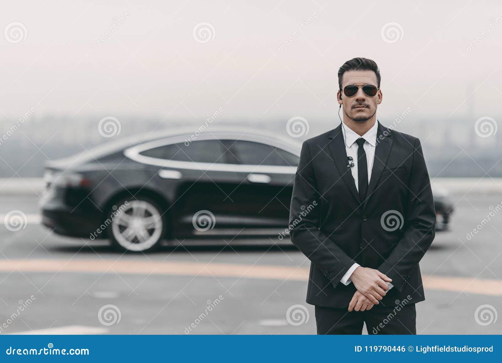 Garde du corps sérieux se tenant avec les lunettes de soleil et l écouteur de sécurité