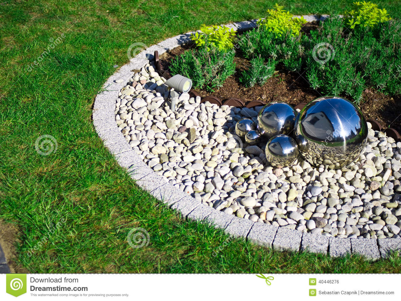 Garden decoration with silver mirror spheres stock photo for Achat cailloux decoration