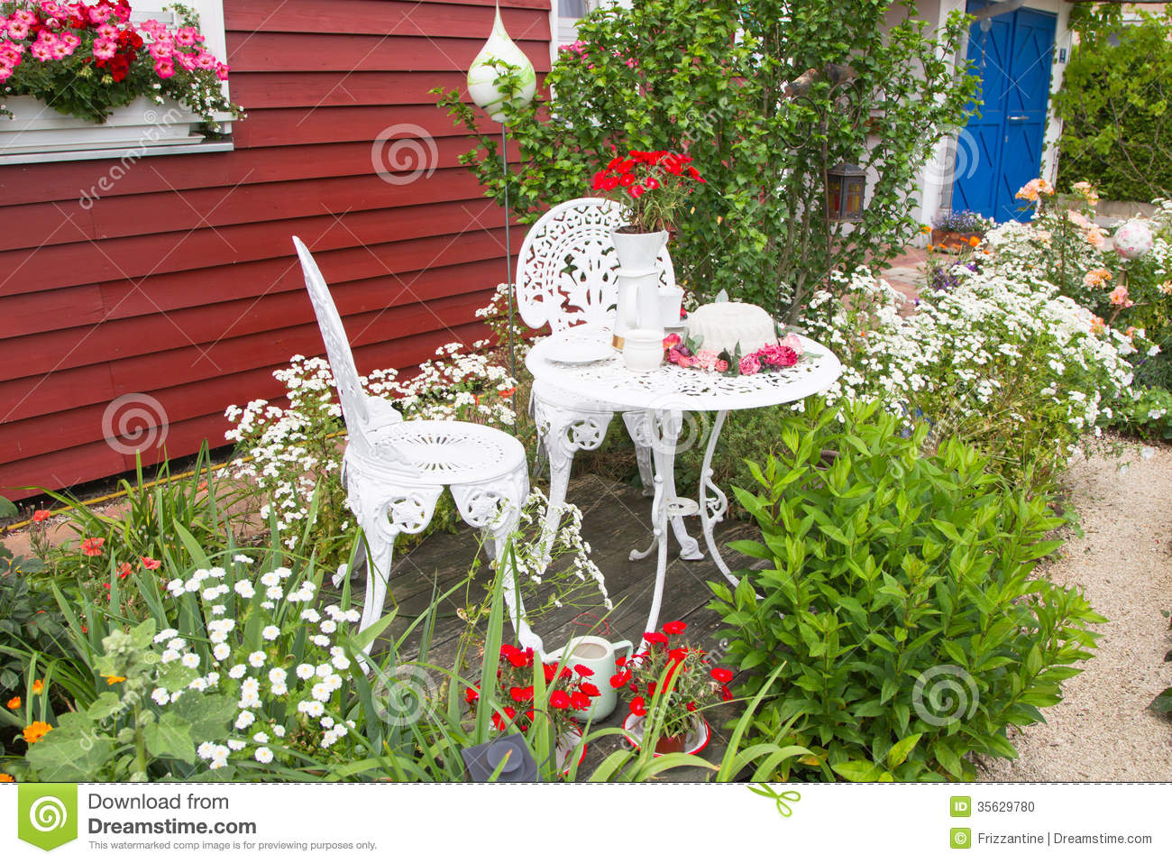 garden furniture set with flowers in front of country house stock photo