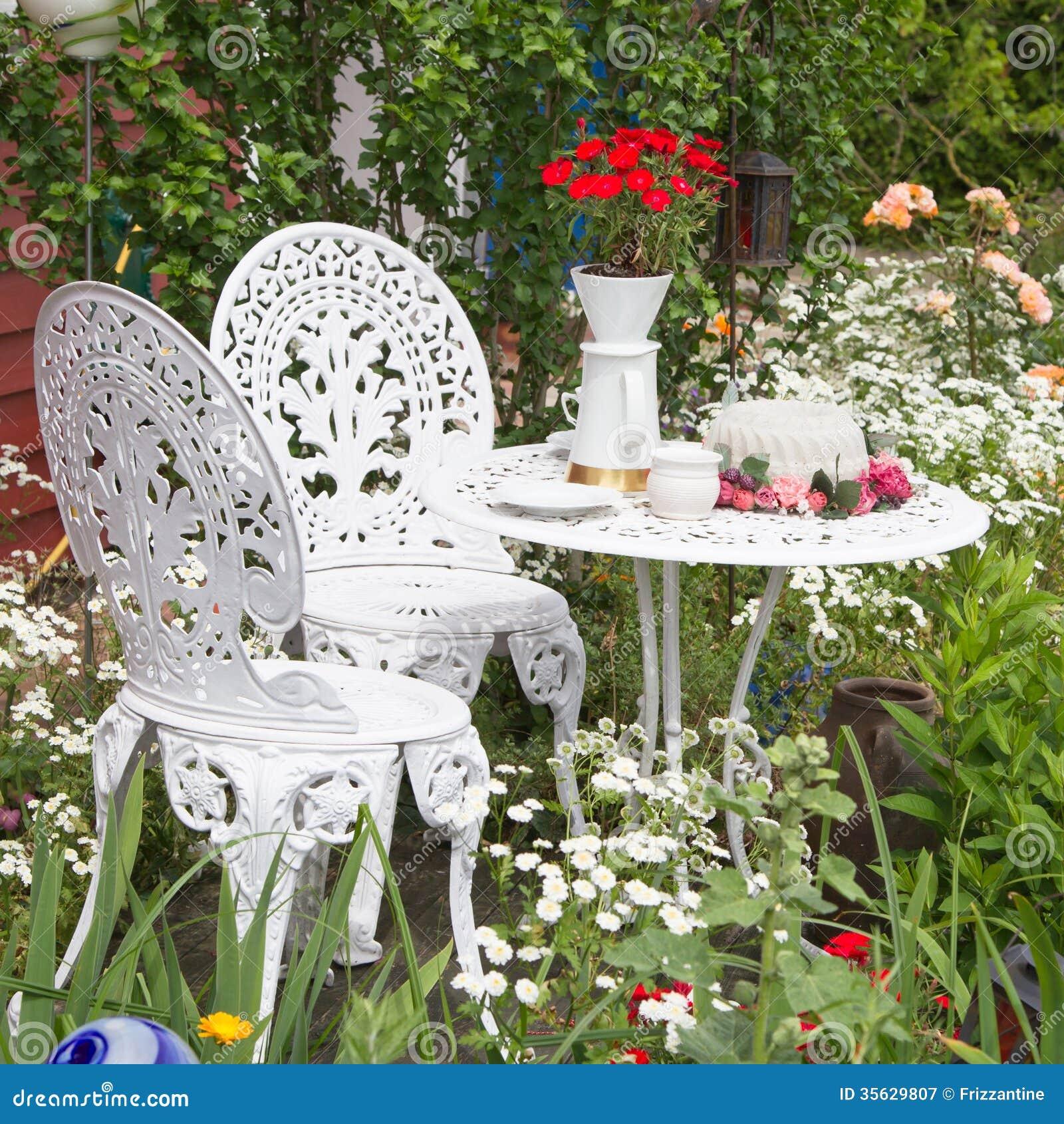 Garden Furniture Set With Flowers Growing In Garden Stock
