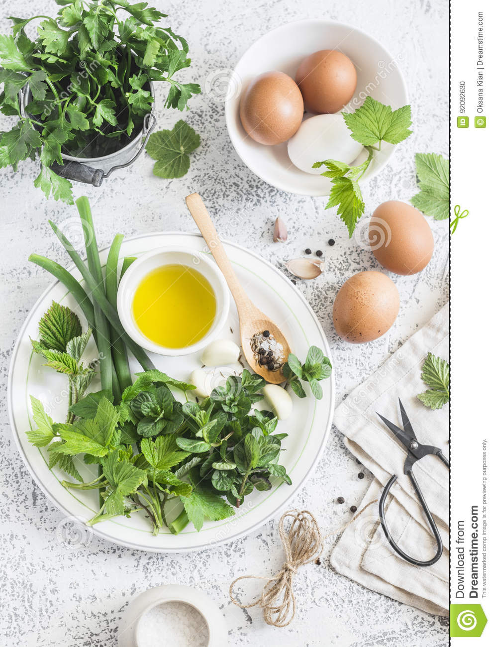 Garden herbs, spices and eggs on a light table. Rustic kitchen still life. Ingredients for cooking. Top view