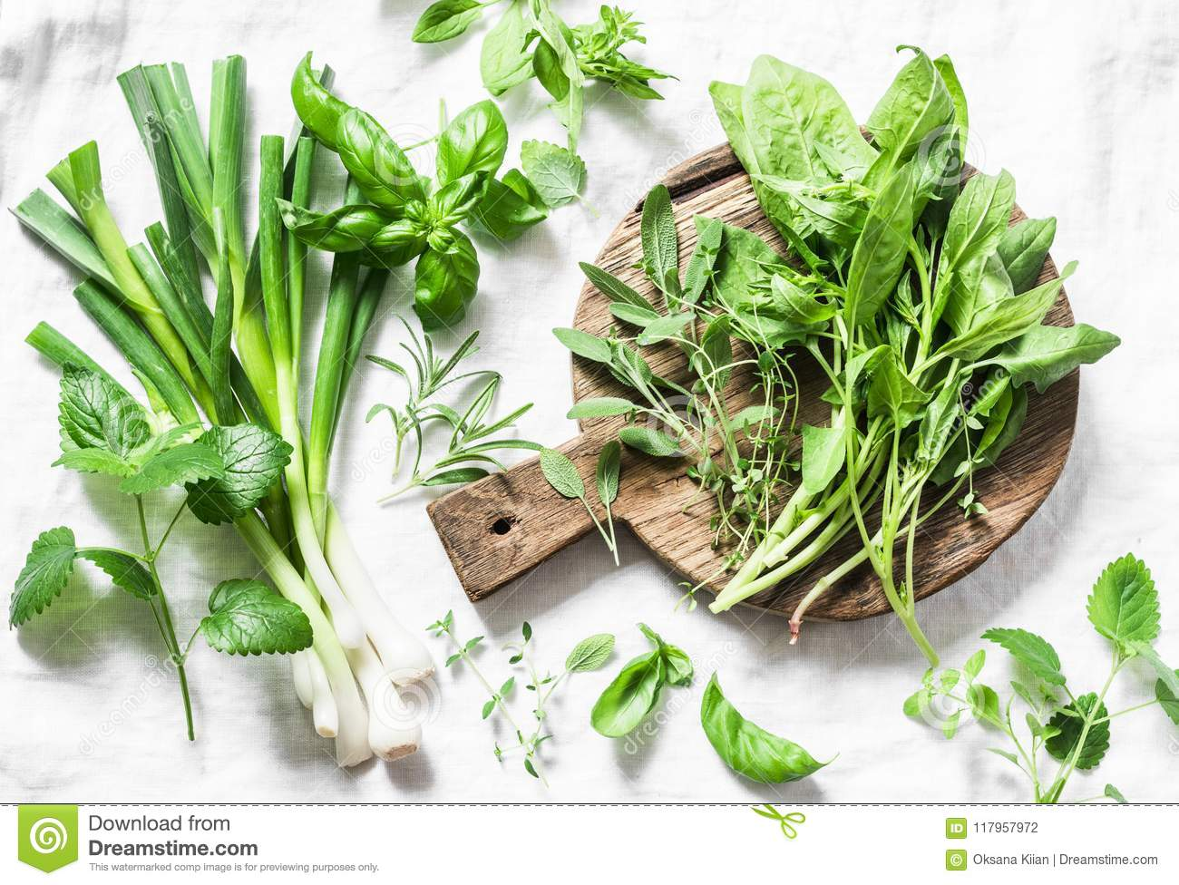 Garden herbs - spinach, basil, thyme, rosemary, sage, mint, onion, garlic on a light background, top view. Fresh food ingredients