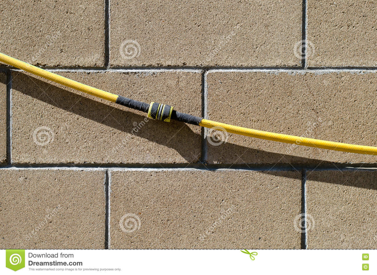 The Garden Hose With The Repair Coupling Hangs On A Wall From Smooth ...