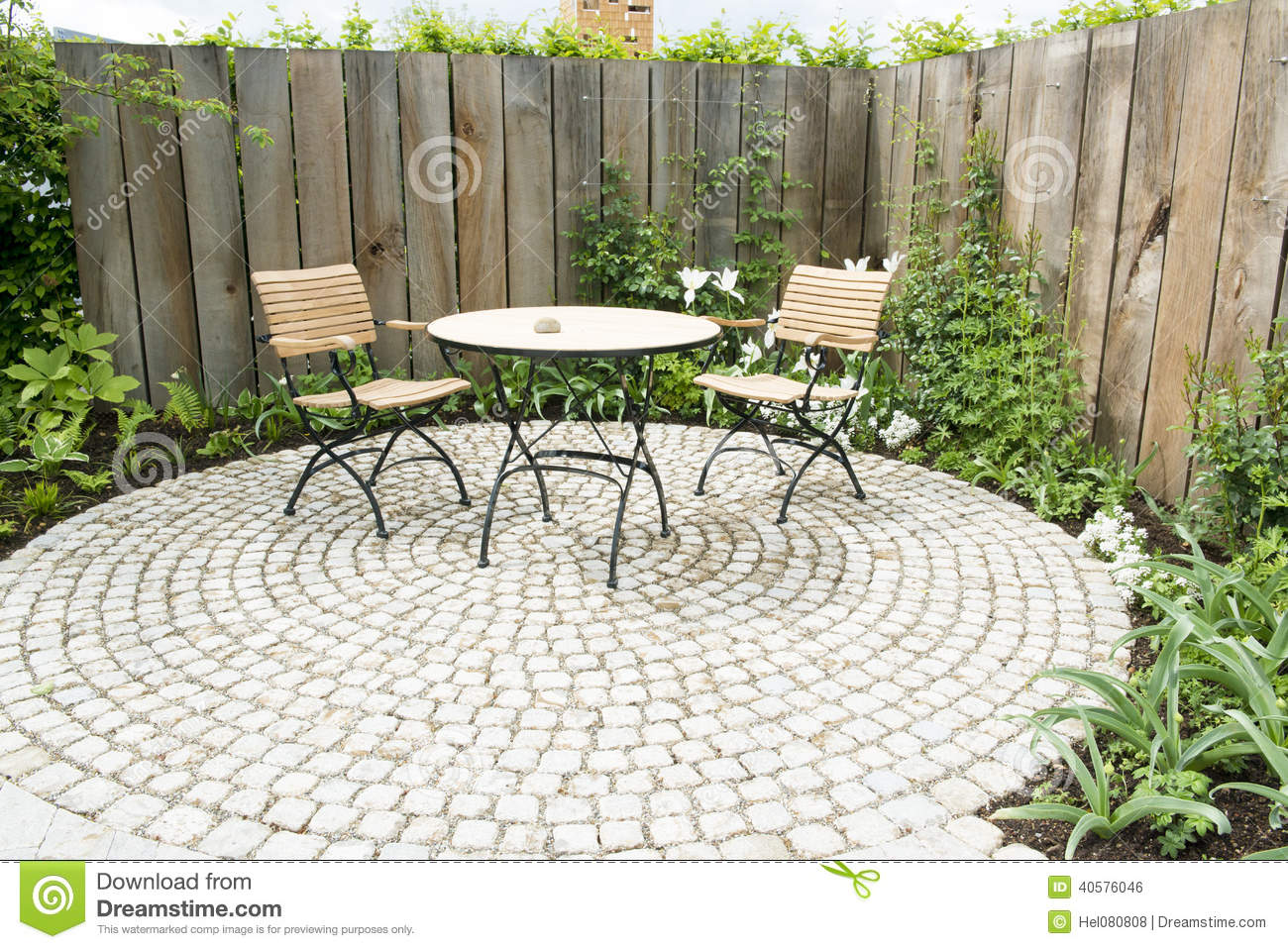 Garden patio with two chairs and round table in front of flowerbed and wooden planks