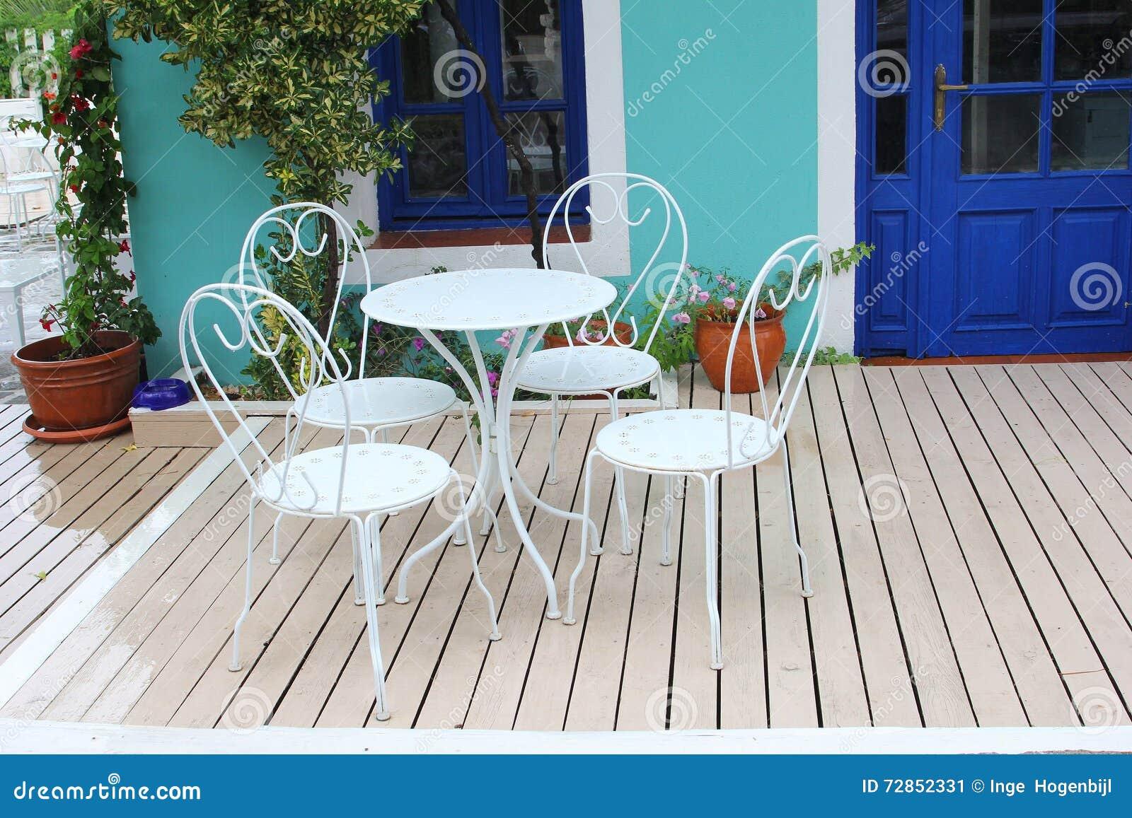 Garden patio with vintage style furniture wooden floor and flowerpots greece
