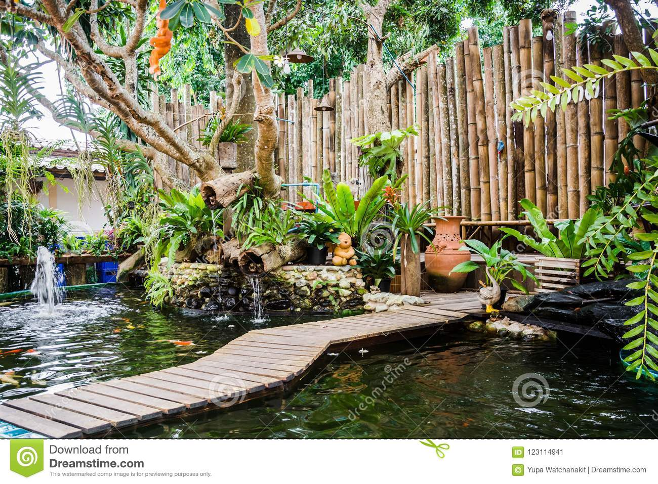Garden With Pond Of Koi Fish And Decorated Bamboo Wall Stock Image
