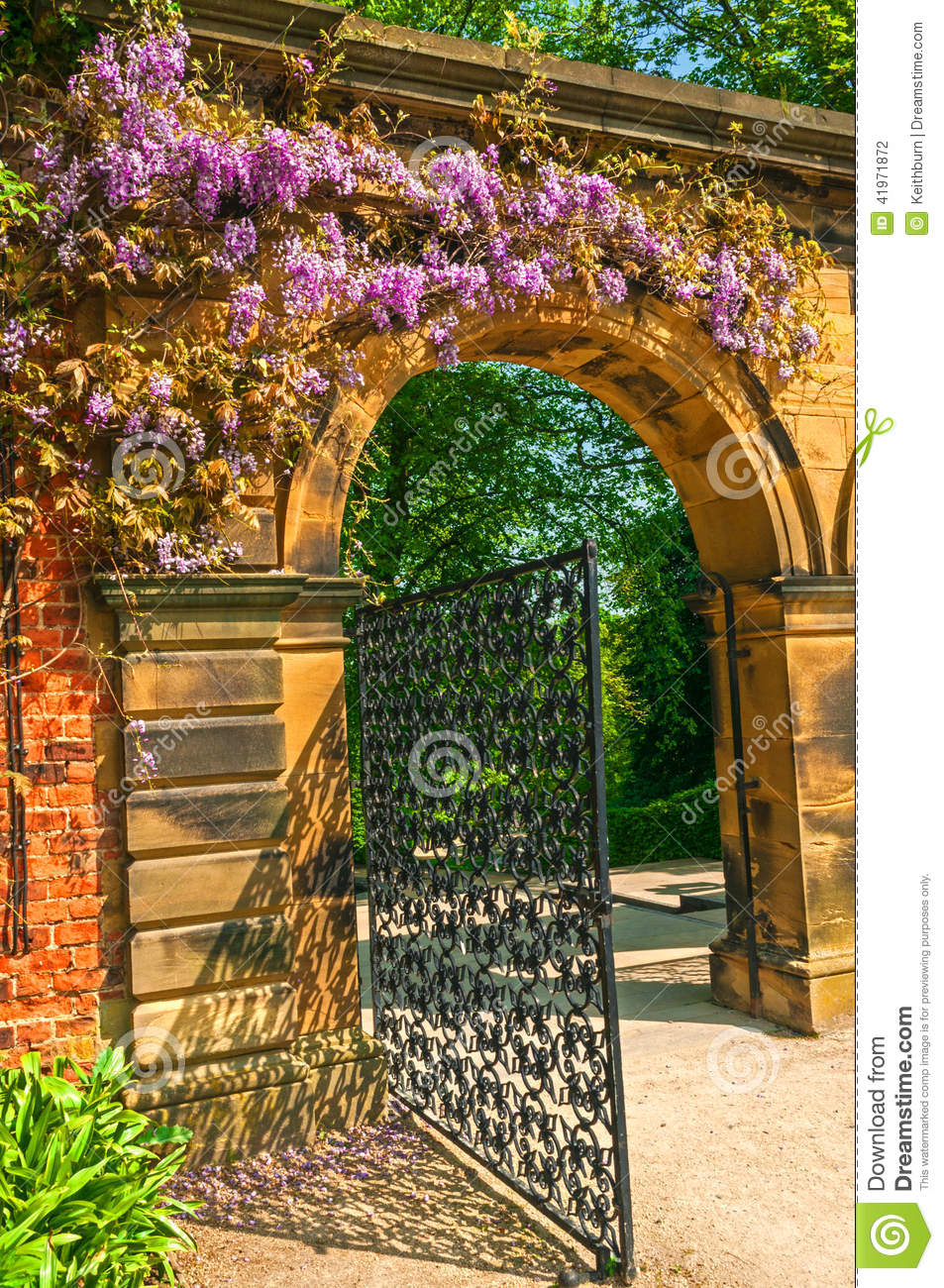 Garden stone arched gateway surrounded by flowers stock for Garden gateway