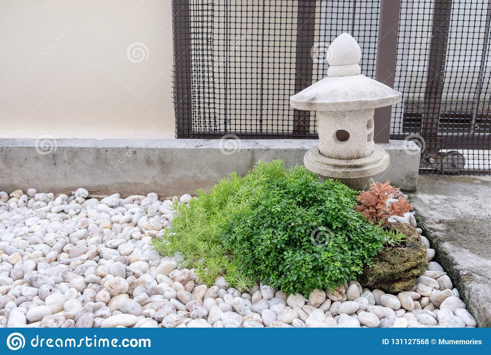Decoration Jardin Avec Pierre garden stone lantern with green bush on white rock stock