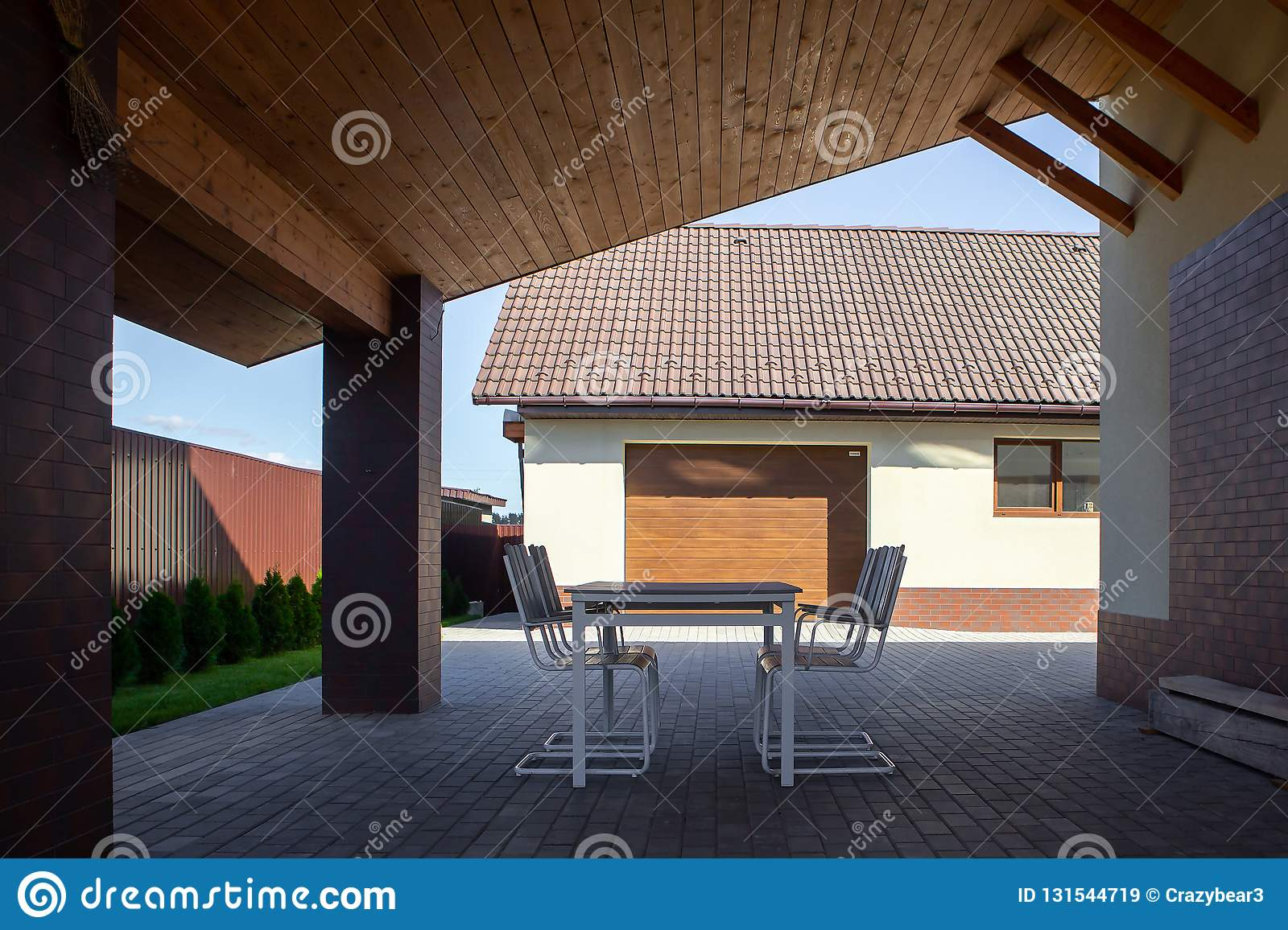 Garden table, chairs stand under a canopy in the shade. Hot sunny day