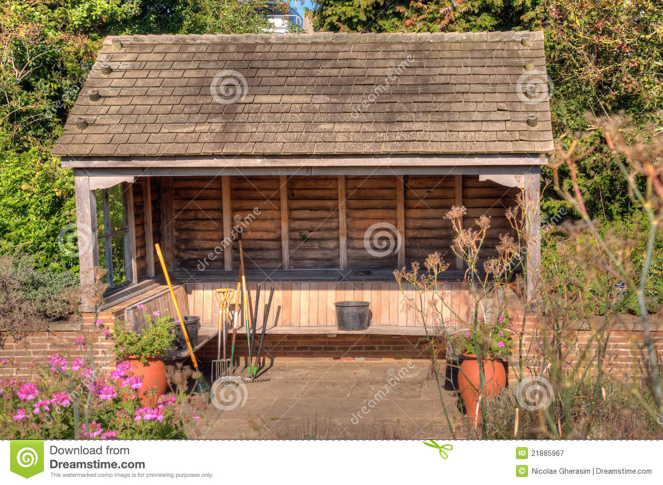 Scenic view of assorted gardening tool in wooden shelter with trees in