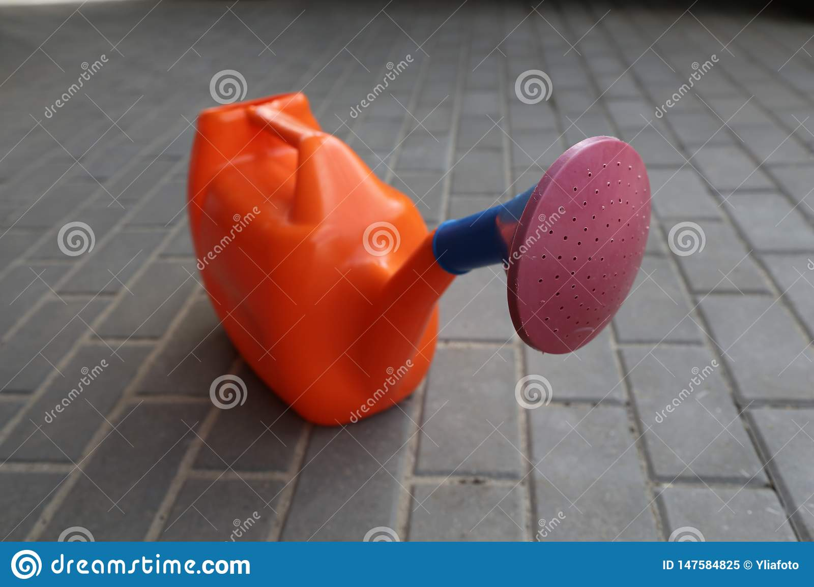 Garden watering can of orange color with a claret tip costs on a tile
