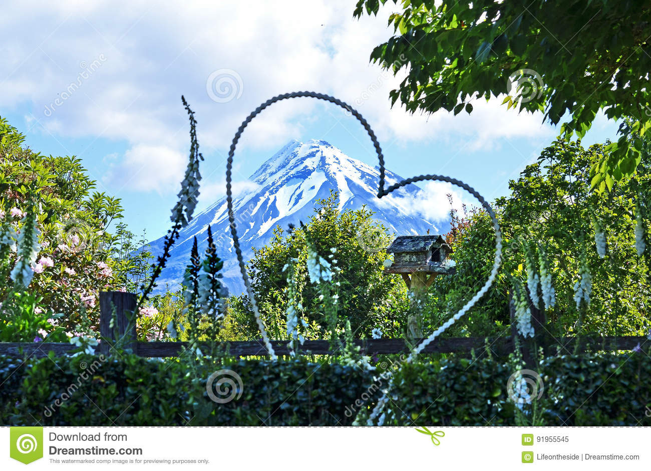 Garden wedding setting & giant floral heart front of snow capped mountain