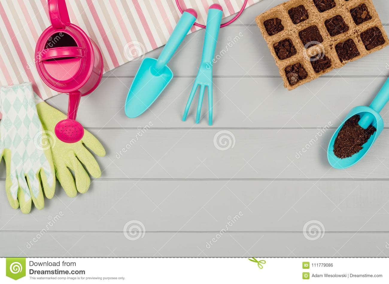 Gardening tools on gray wooden table background top view