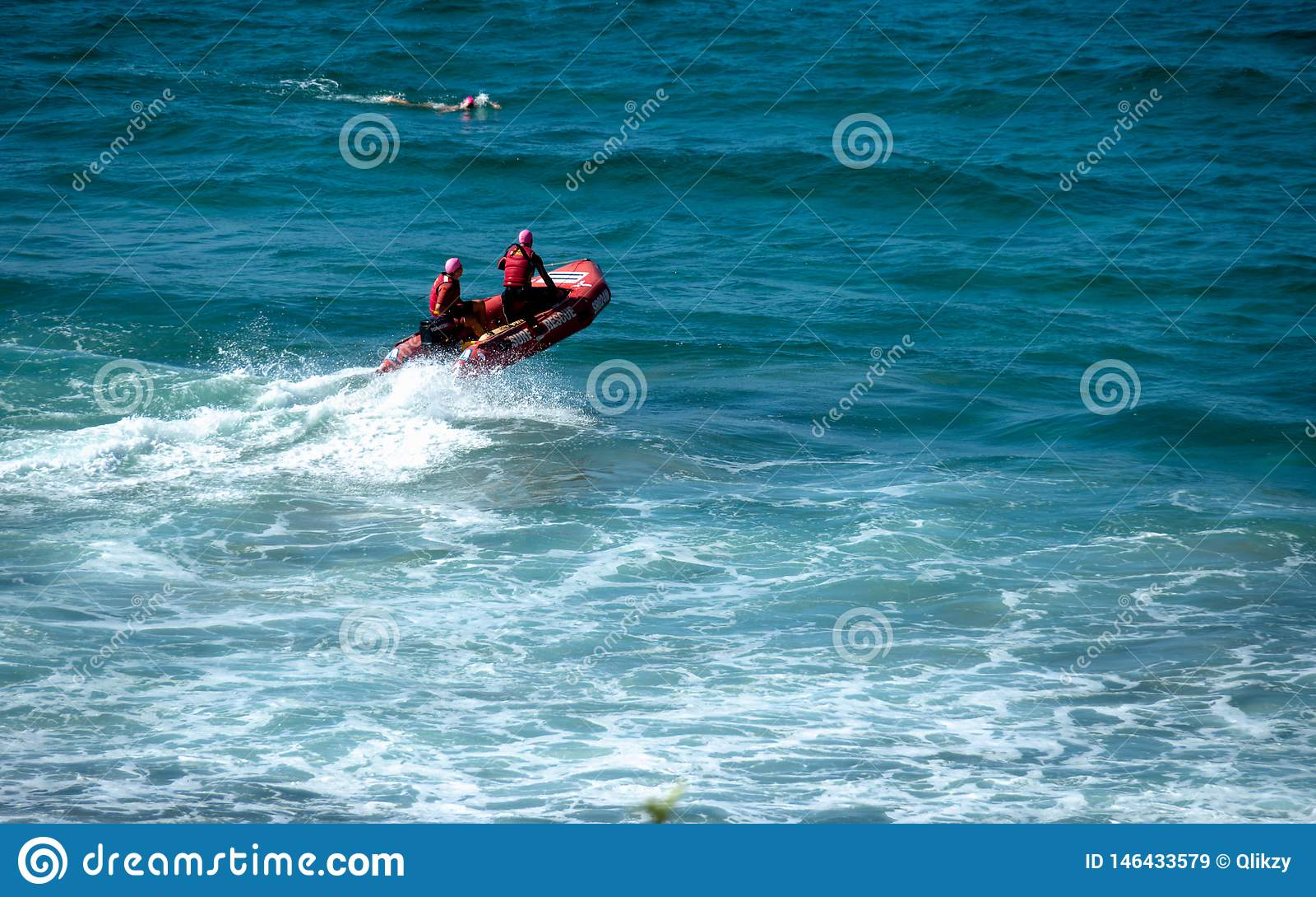 Gardes forestières de plage sur un bateau de sauvetage rouge un surfer nageant tout près