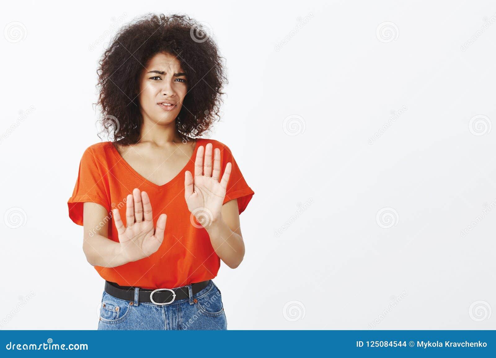 Gardez-le à partir de moi Étudiante attirante intense dégoûtée avec la peau foncée et la coupe de cheveux Afro, tirant des paumes