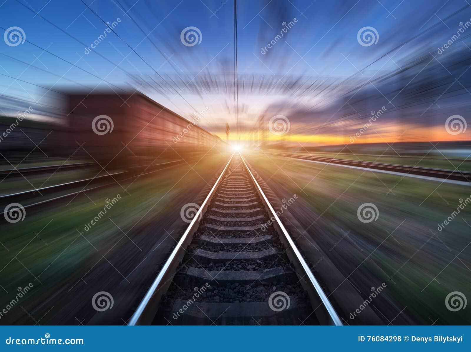 Gare ferroviaire avec des chariots de cargaison dans l effet de tache floue de mouvement au coucher du soleil