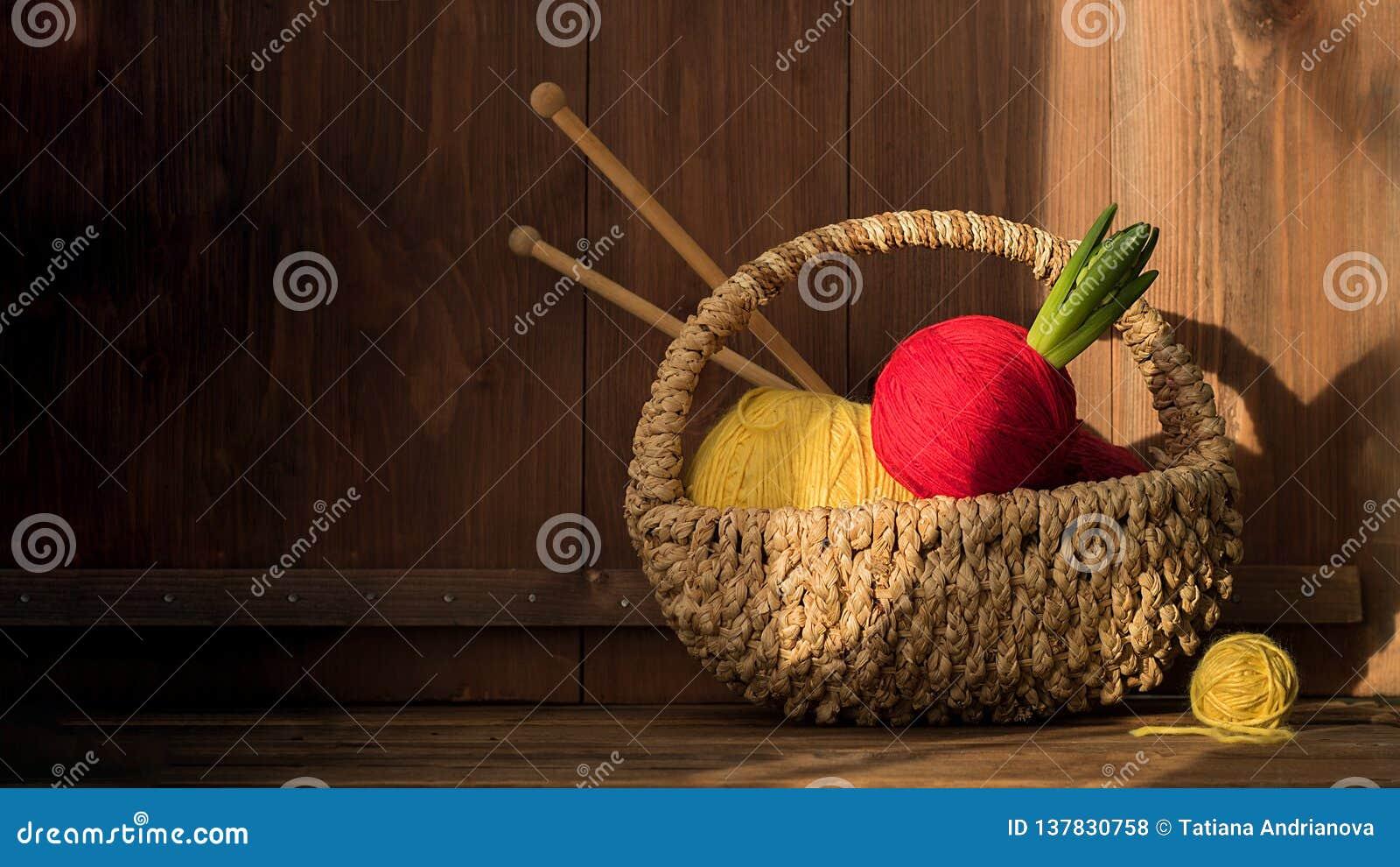 Garen met hyacint in mand met het kniting van stokken op oude houten achtergrond wijnoogst