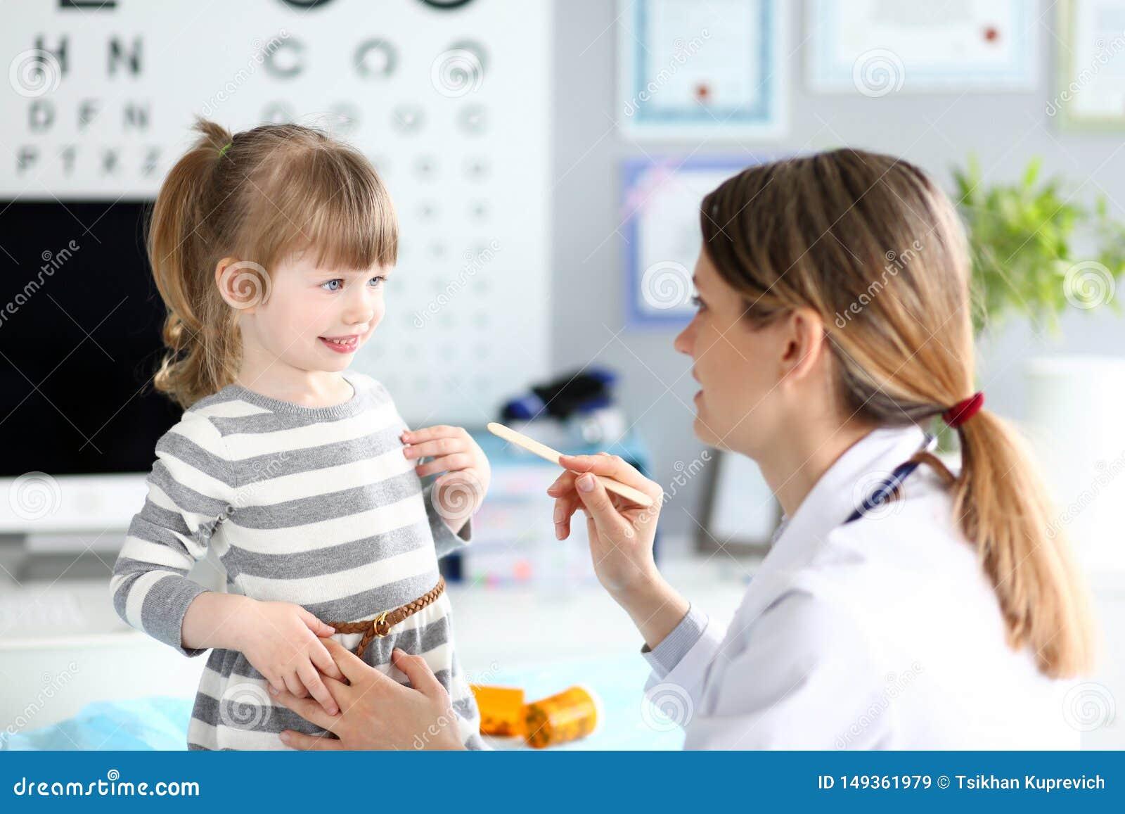 Garganta paciente de exame da crian?a do paediatrician f?mea com vara de madeira