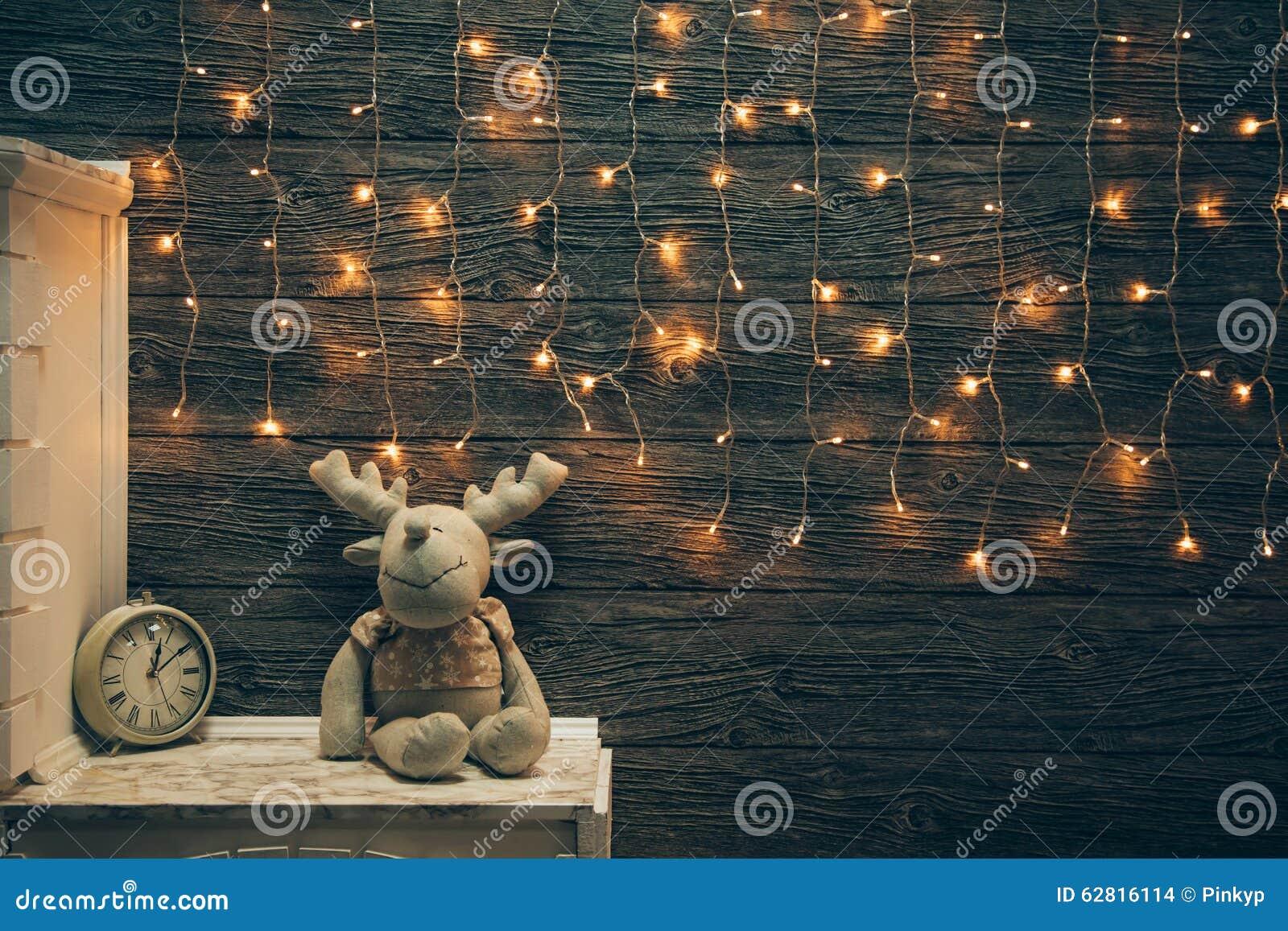 Garland Lights, toy deer, alarm clock on old grunge wooden board