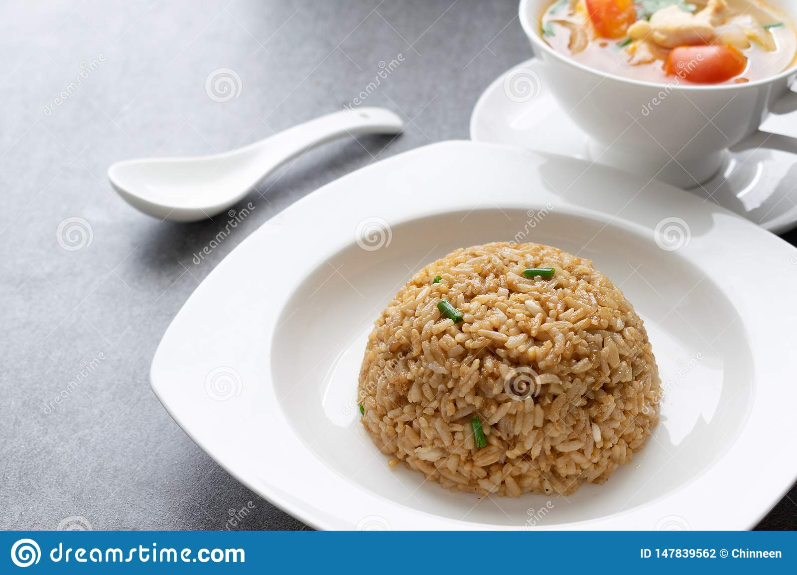 Garlic fried rice and hot soup chicken healthy at morning on concrete table