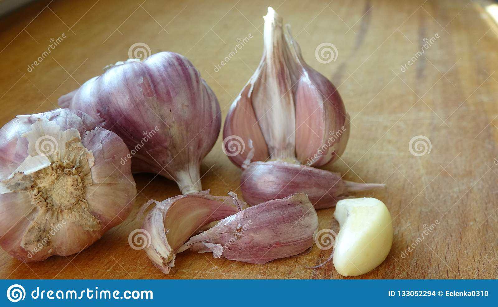 Heads Of Garlic On A Wooden Board Lie On The Table  Whole