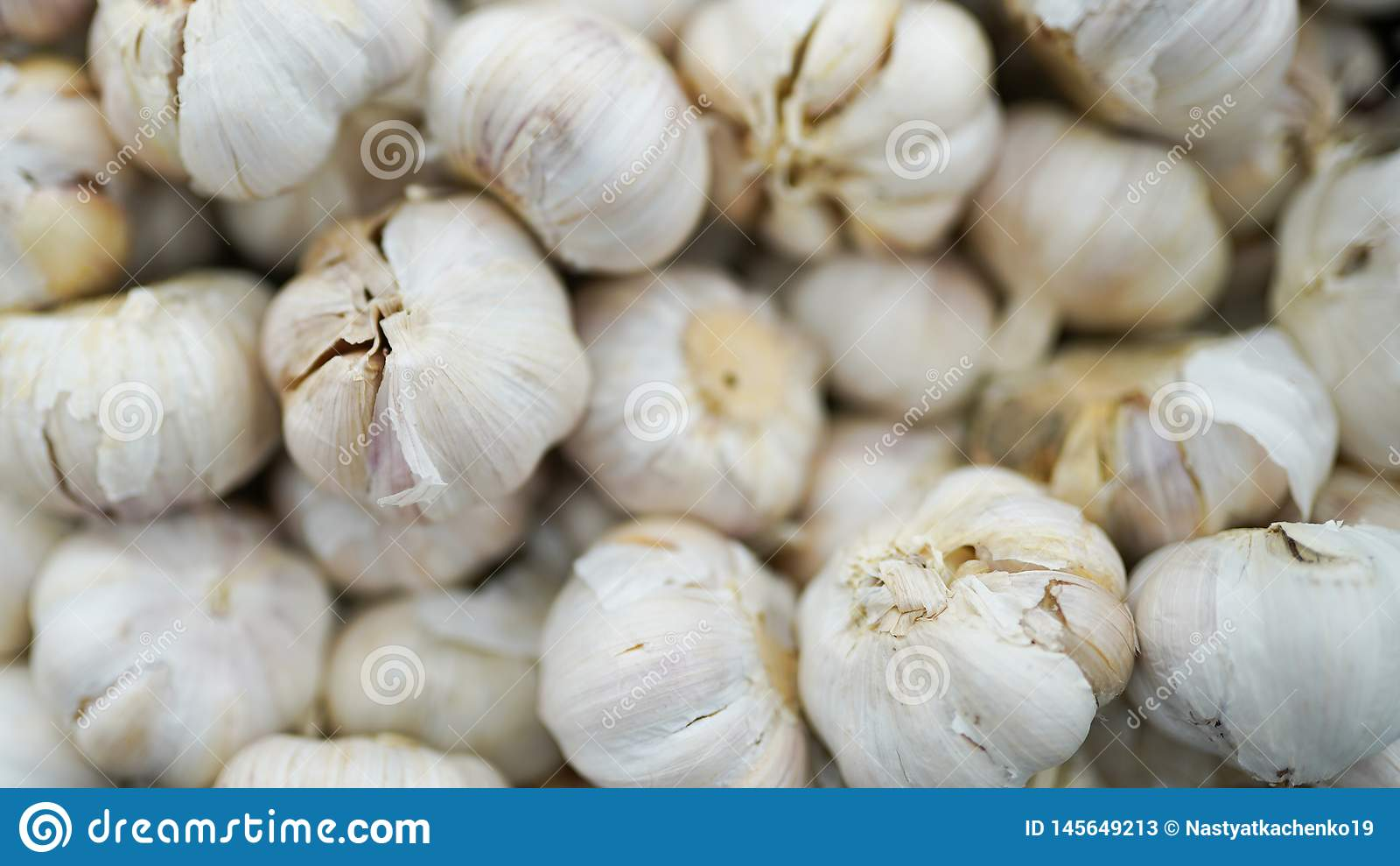 Garlic pile texture. Fresh garlic on market table close-up photo. Vitamin healthy food spice image