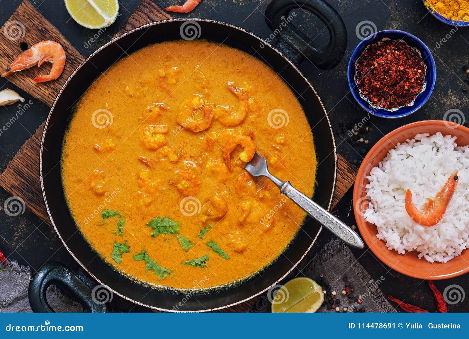 Garnalen met kerriesaus in een pan op een donkere achtergrond Thaise, Indische schotel Aziatisch Voedsel