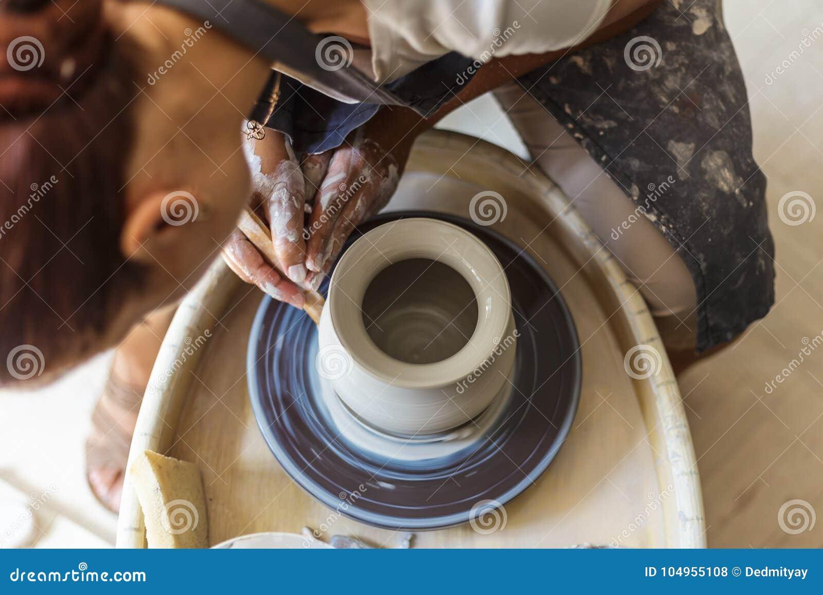 Garncarka robi ceramicznemu garnkowi lub wazie na ceramicznym kole