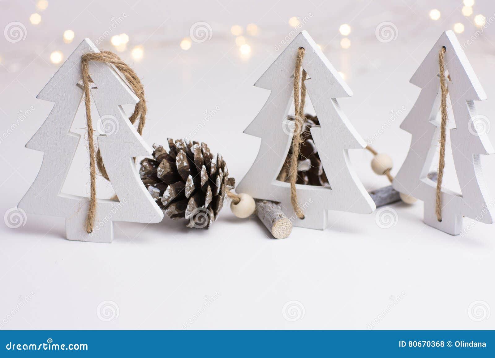 Garnering för vit jul i scandinavian stil med wood grantreeas och sörjer kottar, bokehljus i bakgrunden