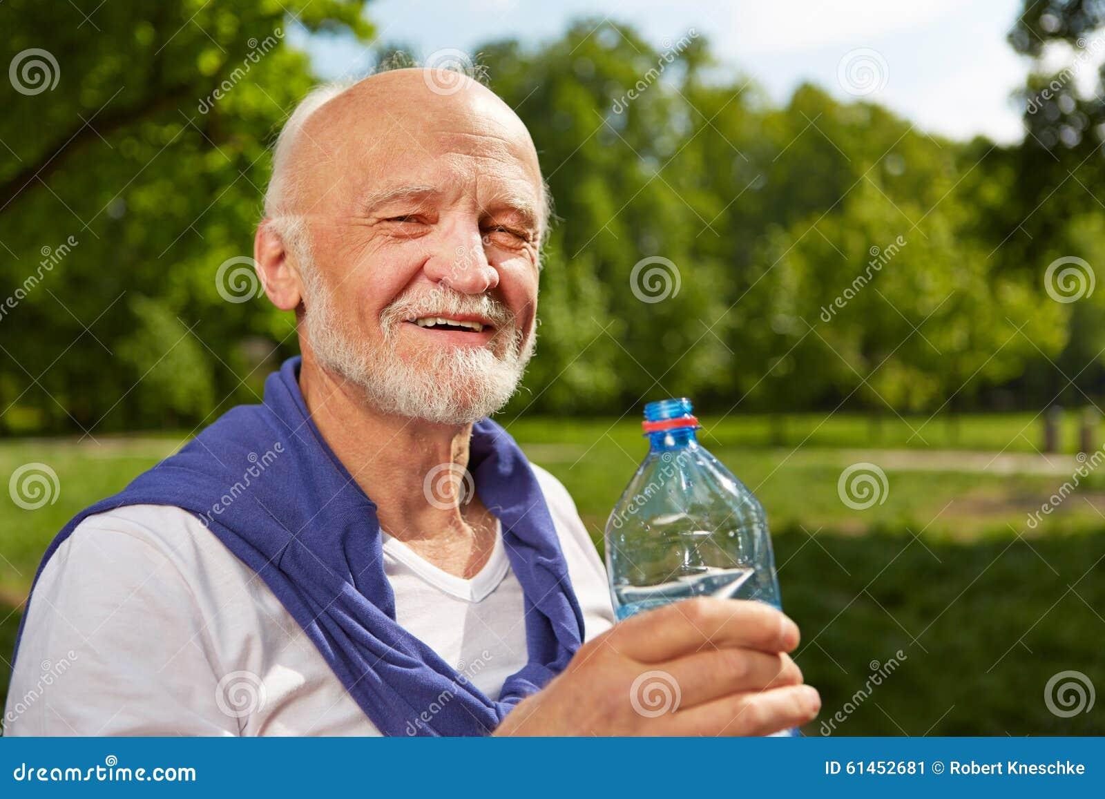 Garrafa bebendo do homem superior da água no verão