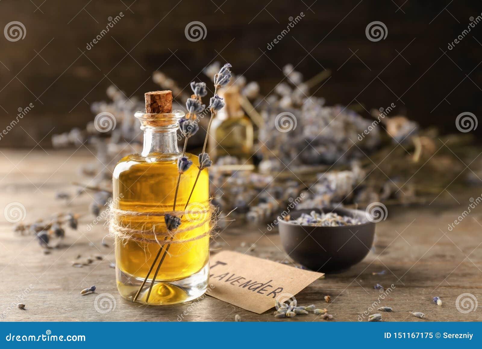 Garrafa com óleo essencial da alfazema na tabela de madeira