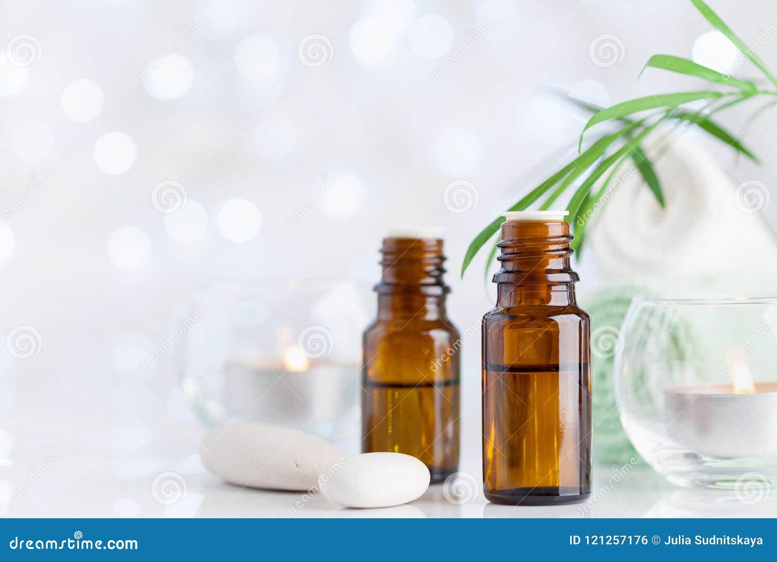 Garrafa com óleo essencial, toalha e velas na tabela branca Termas, aromaterapia, bem-estar, fundo da beleza