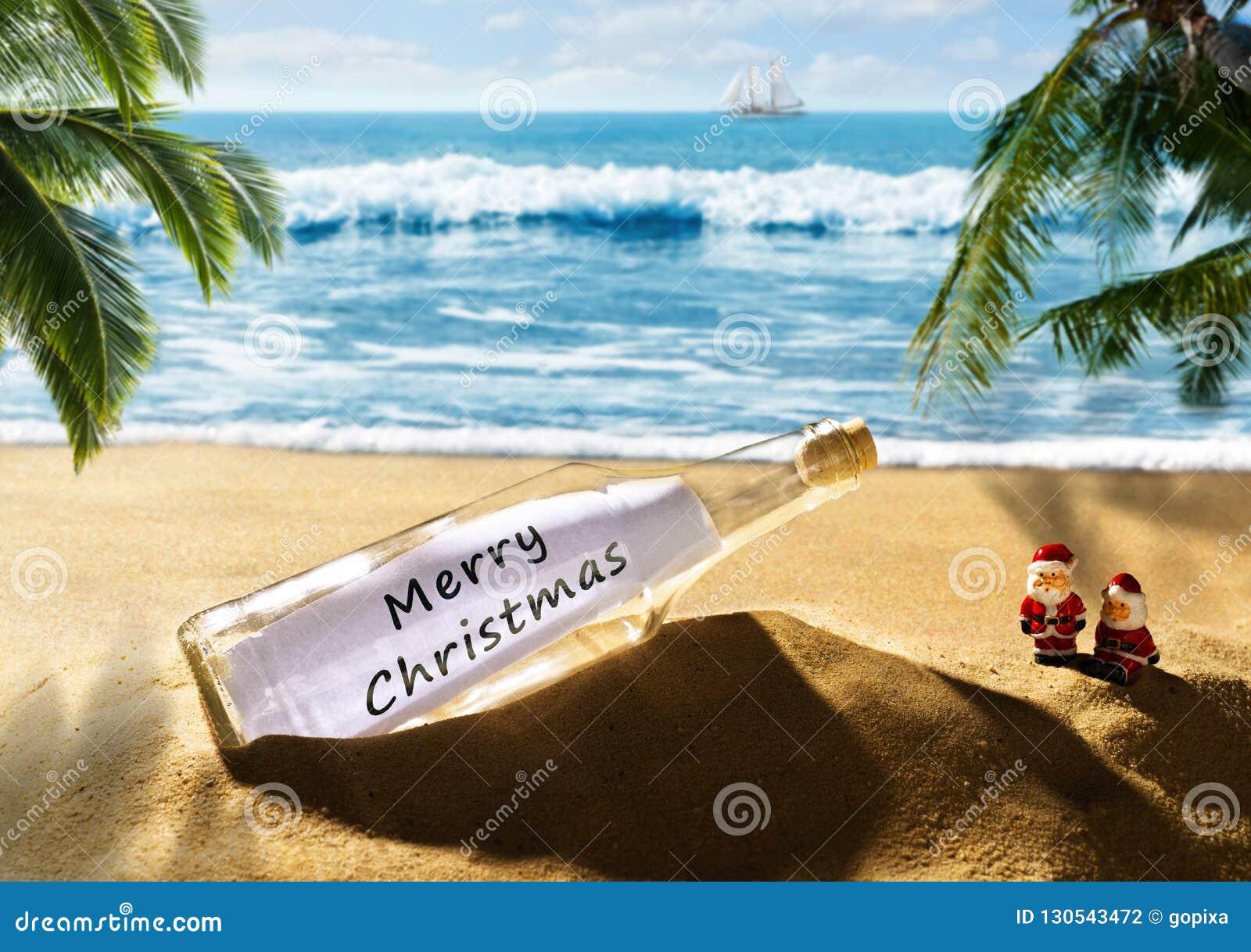 Garrafa com o Feliz Natal da mensagem na praia