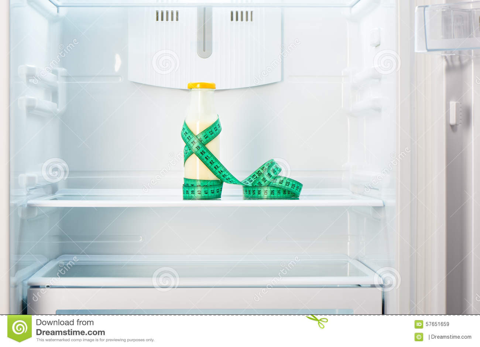 Garrafa de vidro do iogurte com a fita de medição na prateleira do refrigerador vazio aberto
