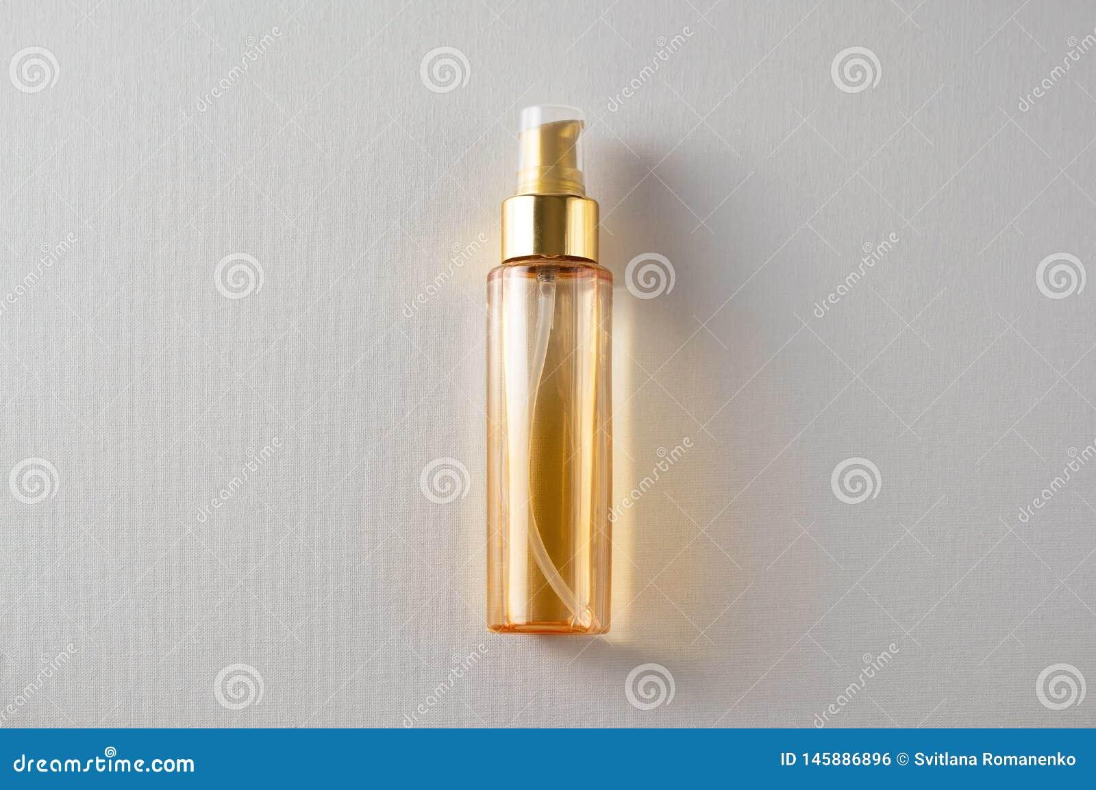 A garrafa do óleo cosmético amarelo em cima