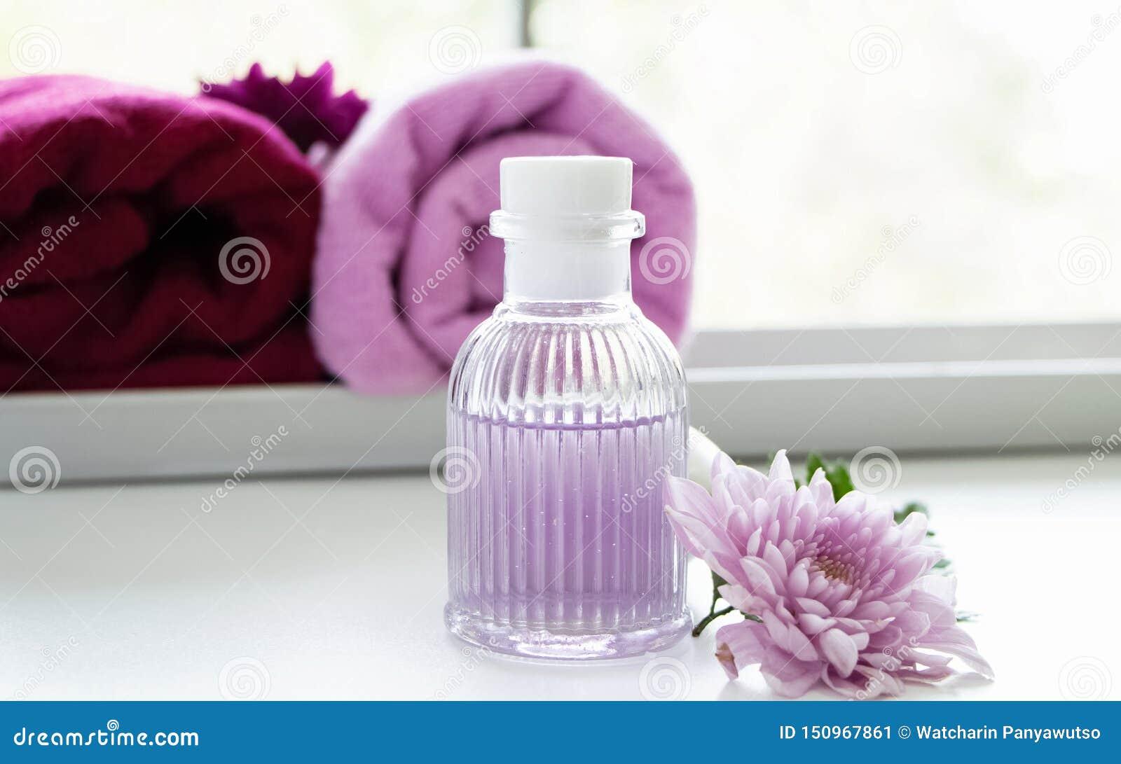 A garrafa do óleo da massagem posta ao lado da flor cor-de-rosa, aromatheraphy