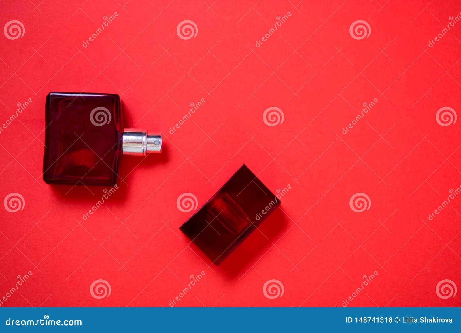 Garrafa do perfume no fundo vermelho