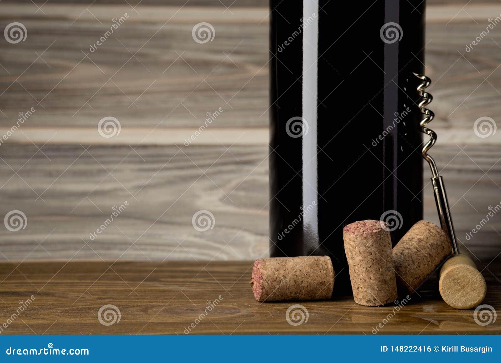 Garrafa do vinho tinto com um corkscrew e corti?a Em uma tabela de madeira