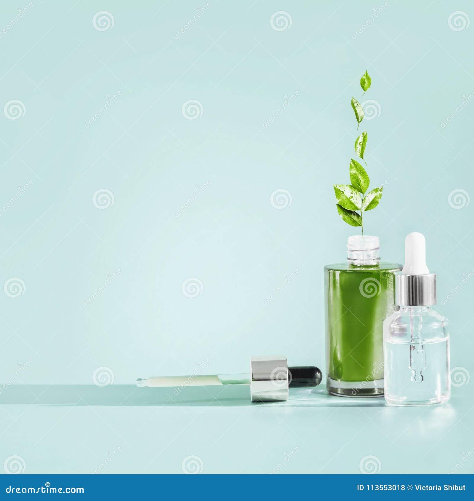 Garrafa dos cosméticos dos cuidados com a pele com conta-gotas e pipeta no fundo azul Soro ou produtos petrolíferos naturais com
