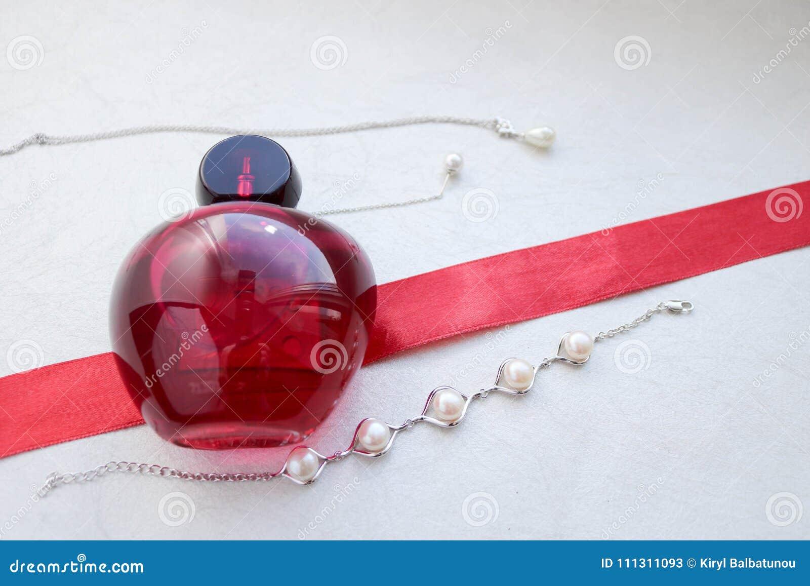 Garrafa glamoroso elegante transparente de vidro bonita vermelha dos perfumes fêmeas que encontram-se em uma fita vermelha com pé